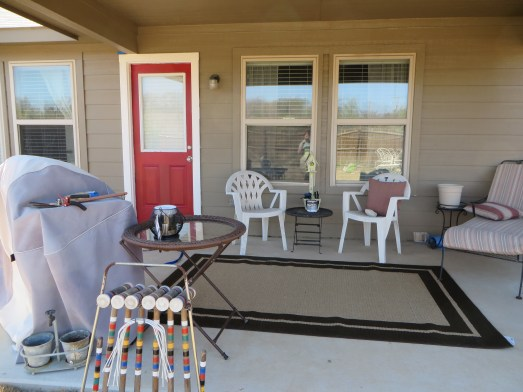 After: covered patio with a bright door and a cushy outdoor rug