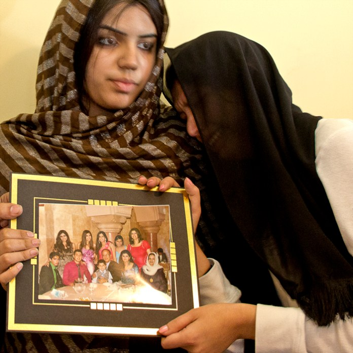 On Friday April 13, 2012, Michelle Arian (left), and Nelofar Arian (right) hold up a family portrait including Abdul Arian who is seen wearing a red dress shirt, just two days after Abdul was shot and killed by LAPD during a pursuit which ended on the 101 North-bound after running a red light and continuing to drive erratically. Photo: Kristen Aslanian