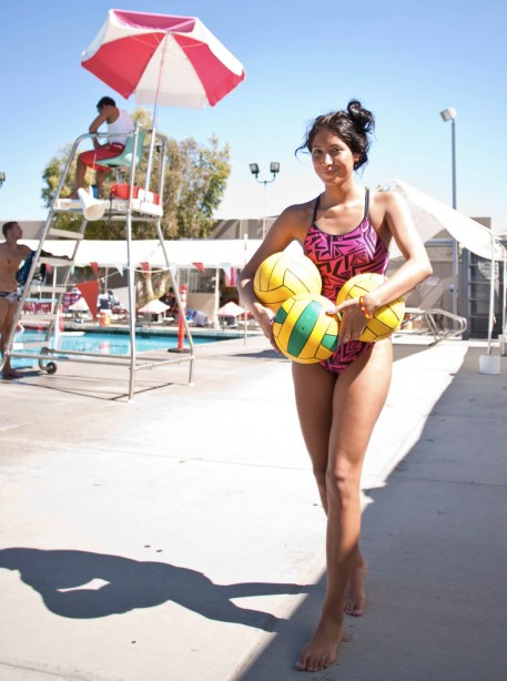 Newly formed women's water polo team member Sabba Giba returns practice balls to the storage area of the Schofield Aquatic Center.