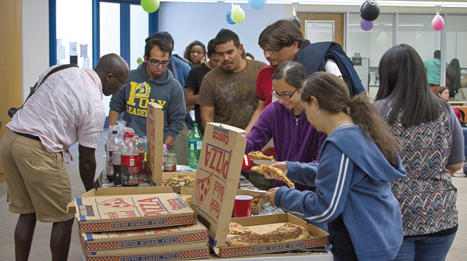 Students line up to grab  pizza during Student Celebration Day. The ASO organizes the event in their office, as part of the end of semester celebrations. May 14, 2014. Photo: Erick Ceron