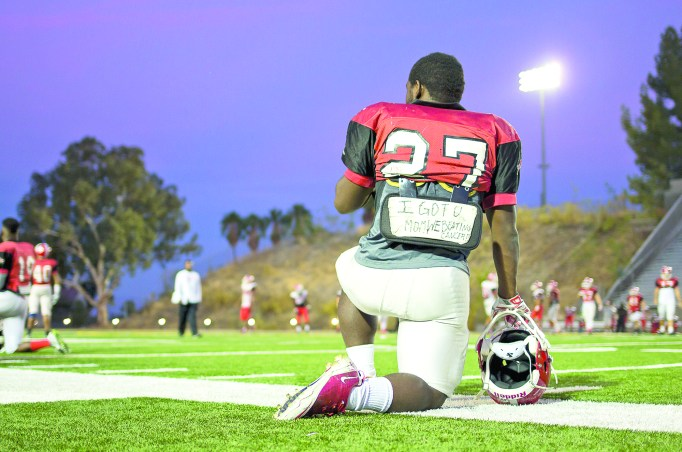 "Robert Fowlkes, a running back for Pierce College, takes a knee during practice at John Shephard Stadium of Pierce College in Woodland Hills, Calif., Oct. 22, 2014. Fowlkes' is currently fighting a rare form of cancer in her spine. ""I got U mom. We beating cancer,"" is written on Fowlkes backplate. Photo: Nicolas Heredia"