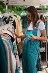 Devin Bachmeier looks through clothes in the Freckle Bug Vintage boutiqe at the Vintage Market at Pierce College in Woodland Hills, Calif., on Sept. 22, 2019. Photo by Katya Castillo.