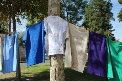 Shirts lined up on string, from tree to tree at Rocky Young Park at Pierce College Woodland Hills, Calif. on Oct. 16, 2019. The Clothesline Project is to bring awareness to domestic violence. Most students either shared their own stories on the multi colored shirts or wrote a positive message for students that have experienced domestic violence. Photo By: Kamryn