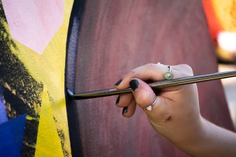 Olivia Parker, Art 308 student, strokes her paint brush down the canvas as she overlooks Pierce College in Woodland Hills, Calif., on Oct. 24, 2019. Photo by Sophia Gomez.