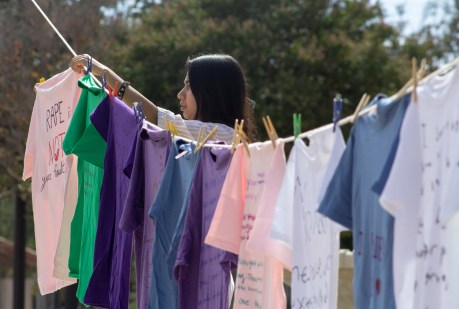 """Bushra Hannan hangs up a shirt that she wrote the message """"Rape is not your fault"""" on a clothesline during the Clothesline Project on Oct. 16, 2019 in Rocky Young Park at Pierce College in Woodland Hills, Calif. Hosted by ASO, the Diversity Committee and B.R.A.V.E., this event brings awareness to survivors of abuse by displaying messages or stories written by students. Photo by Angelica Lopez."""