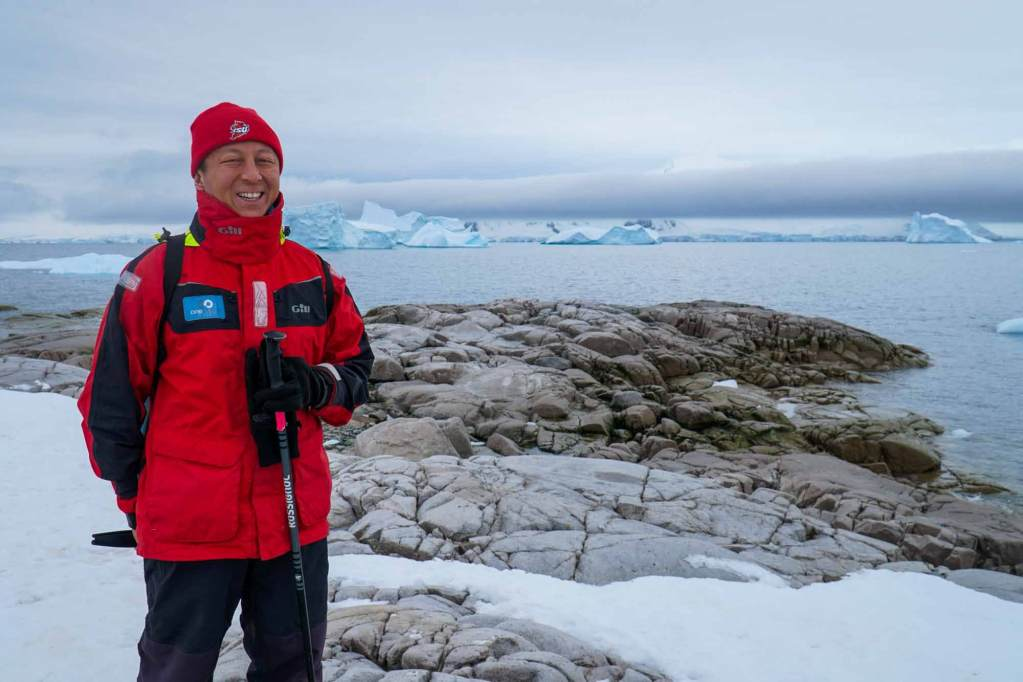 Halef showing you what to wear in Antarctica - a jacket and ski pants