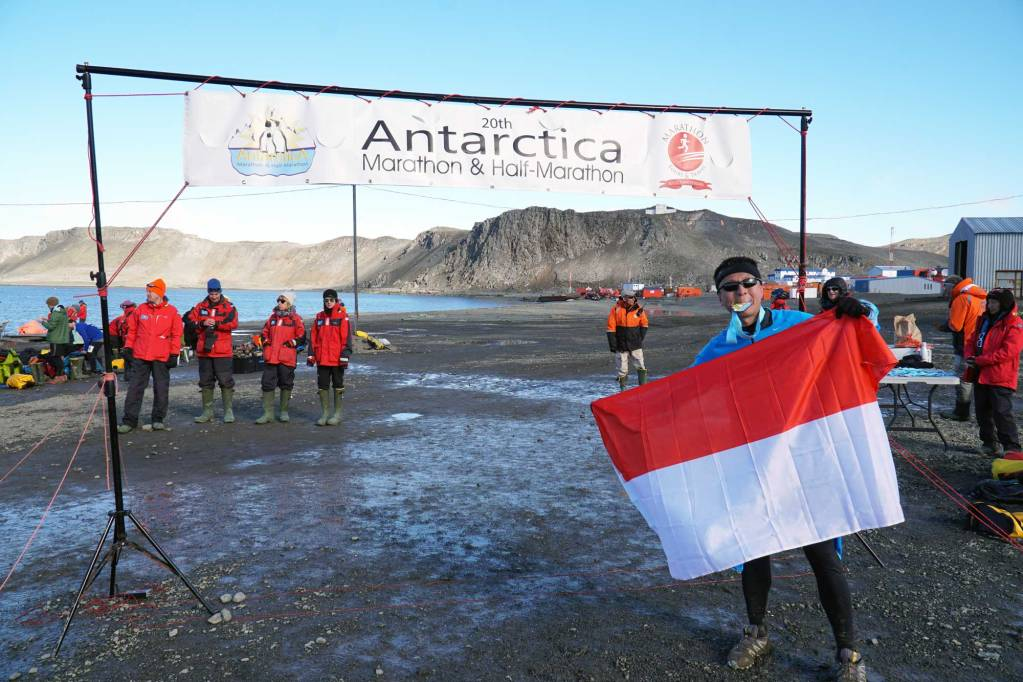 Halef at the antarctica marathon finish line wearing his medal and holding an indonesian flag