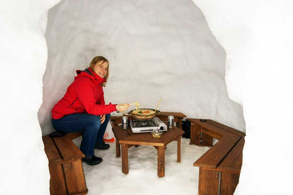 Snow hut of Restaurant Kamakura-Mura with author eating in an igloo