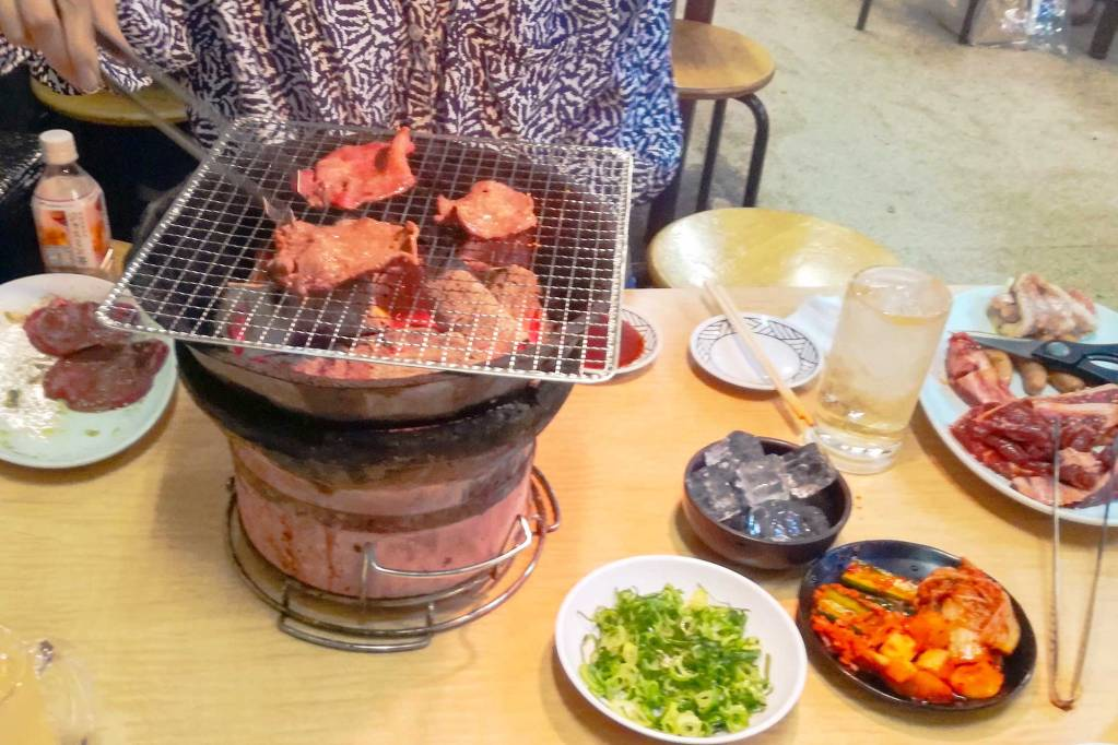 A table with Yakiniku and a grill on top of the table