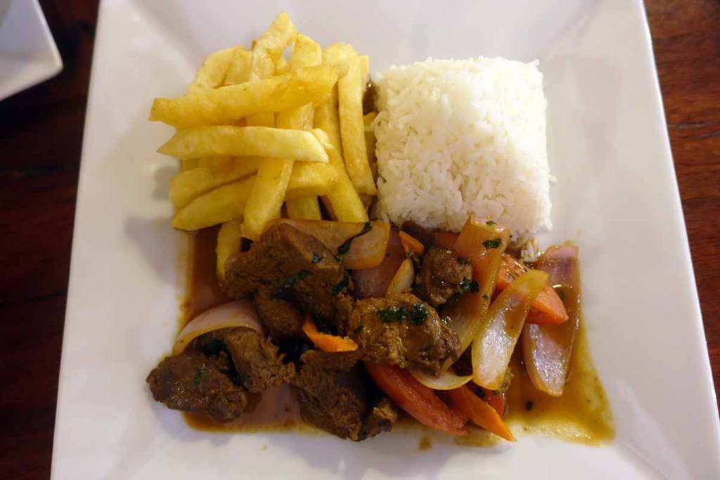 Lomo saltado is some of the most authentic peruvian food you can buy. This one is on a square plate with rice, french fries, and mixed veggies.