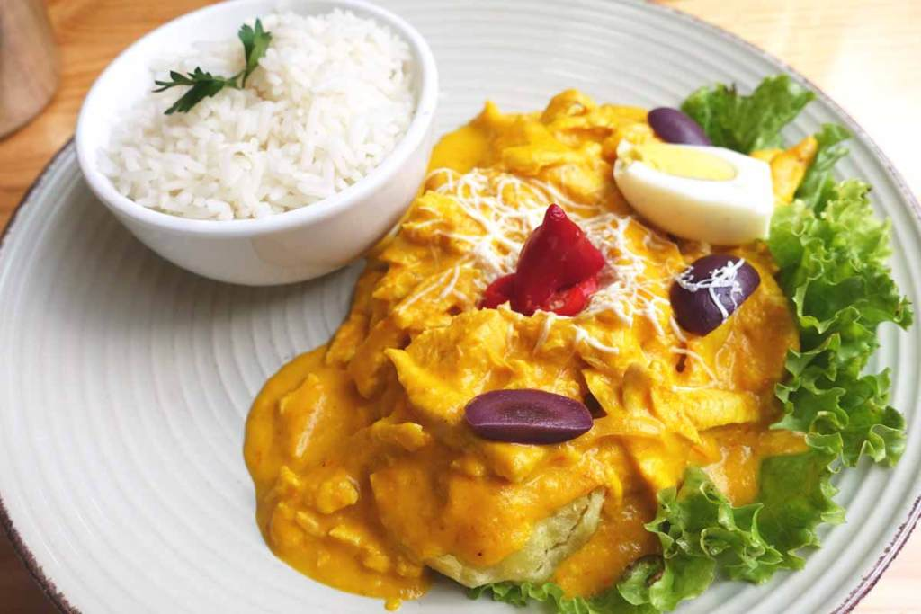A typical serving of aji de gallina. Orange sauce covering chicken chunks with a white bowl of white rice.
