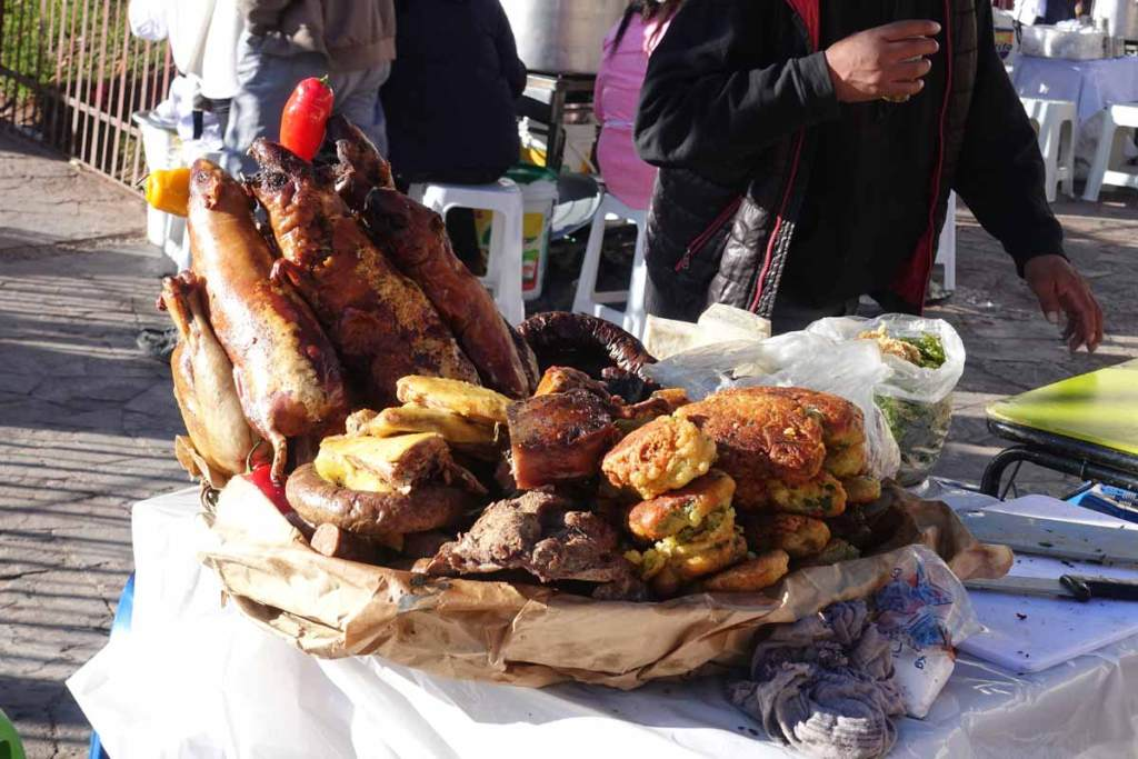 Baked guinea pigs. The most authentic peruvian dish of all. A pile of them on a table at a market.