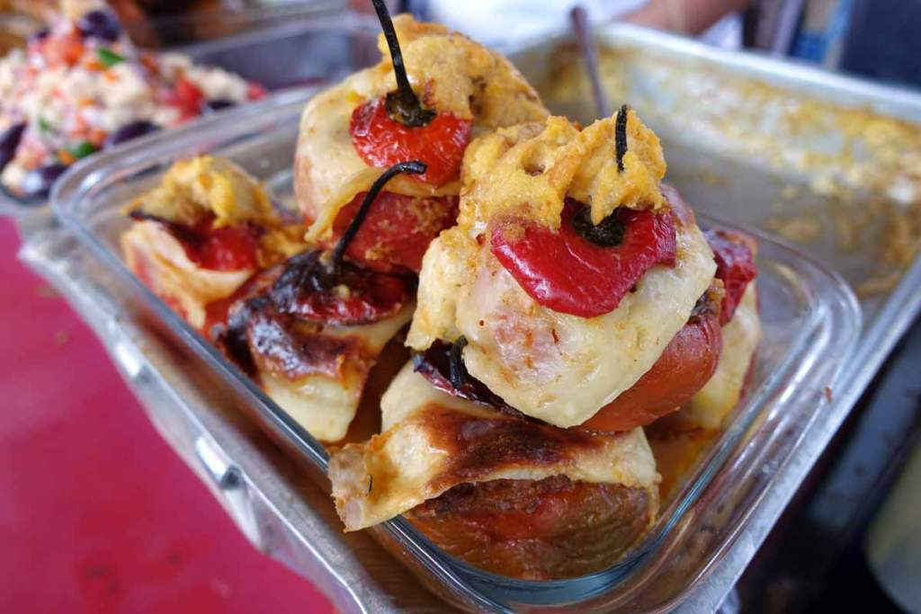 A glass tray with four stuffed red rocoto peppers covered in white melted cheese.