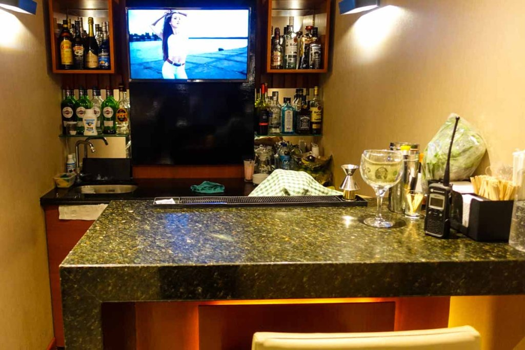 bar with room for one person at hanaq vip lounge. Lots of different styles of alcohol.