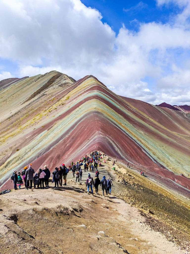 Rainbow mountain from the peak focusing downward on about 50 other tourists