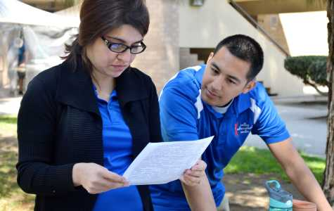 Blanca Casillas and Jonathan Magno, members of the Valley Achievement Center, look over a student's resume at the CSUB Career Fair on April 15. The Valley Achievement Center works with special needs children.