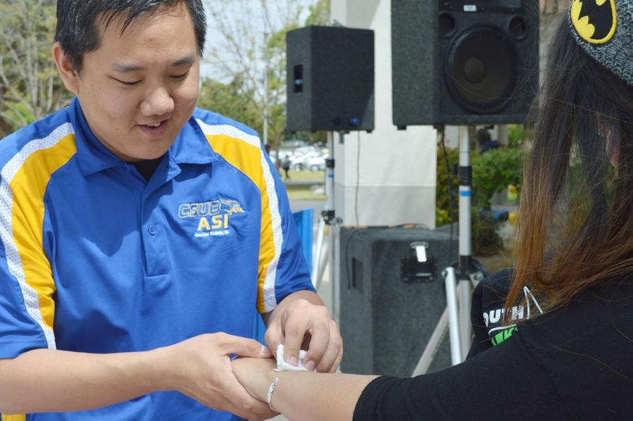 Mike Kwon, ASI and CSUB Fashion Club member, gives Cristal Mondragon, junior, a flash tattoo at the CSUB Fashion Club fundraiser on April 7.