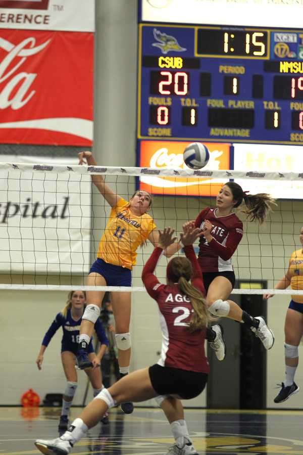 CSUB's Kortney Freeland spikes the ball at the New Mexico State defense in a tight first set in 2015. Photo by AJ Alvarado/The Runner