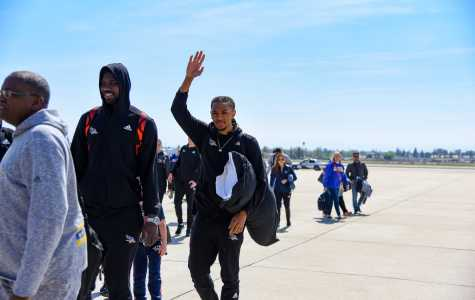 Redshirt-senior forward Matt Smith and redshirt-junior center Fallou Ndoye greet fans waiting for the CSUB men's basketball team's arrival at Meadows Field Airport on March 29.