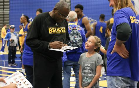 Head coach Rod Barnes autographs books for community members who attended the last home practice.  By Karina Diaz/The Runner