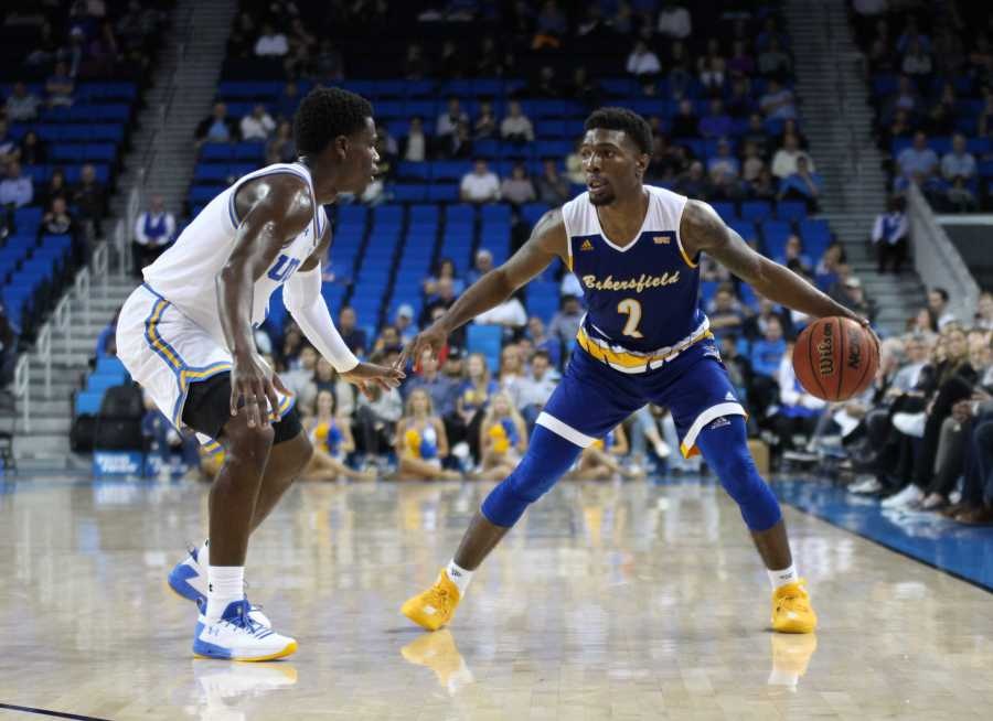 Holden surveys the floor as he is defended by UCLA junior guard Aaron Holiday. All Photos by Peter Castillo/ The Runner