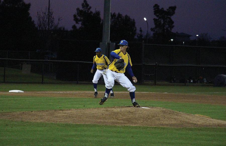 CSUB's starting pitcher, #36 Kyle King makes a pitch as third baseman, #26 Daniel Carrizosa looks on.