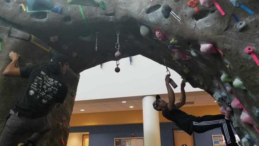 Randy Arevalo and Trent Cardenas climb on The Rock at the Student Rec Center on Feb. 14 during the partner climb night.  Sam Underwood/The Runner