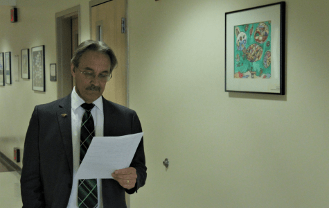 Steven Bacon, Dean of Social Sciences & Education, reads and walks down the halls of the Education Building.