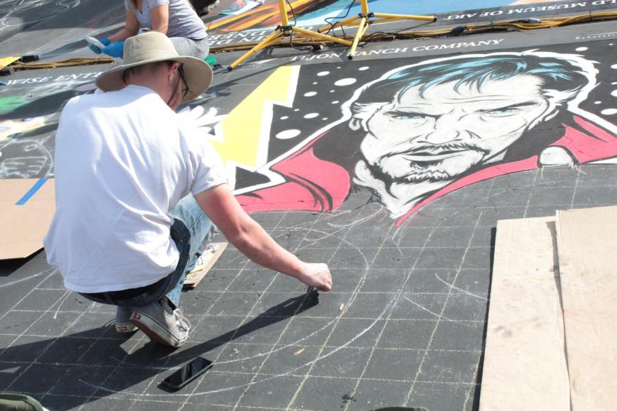 Artist, Jason Henderson, works on his chalk work of Doctor Strange on Day 1 of Via Arté at the Market Place.