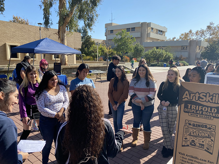 A group of students gather around to answer questions on how they can spot and/or prevent sex trafficking.
