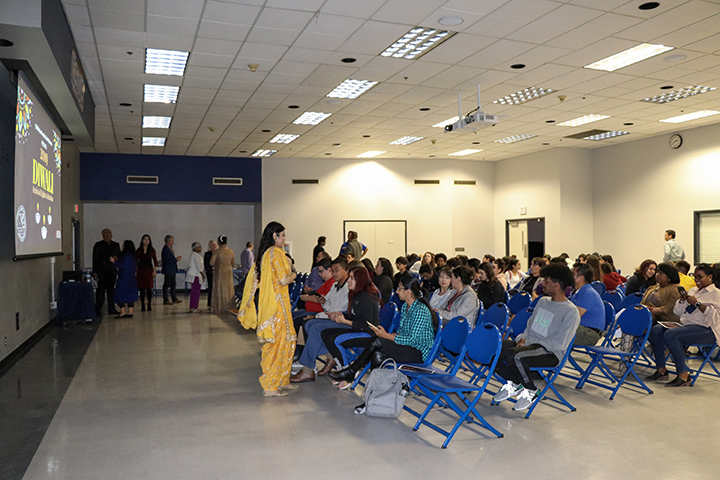 Henna Singh (in yellow) stands in front of the crowd ready to begin the Diwali festival. Singh was the emcee for the event.