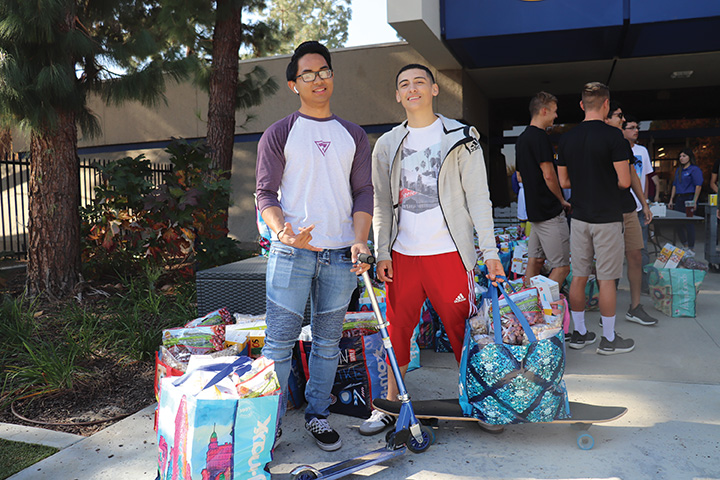 Jorge Moreno (right) and Trent Cardenas (left), were a few of many students who participated in the food distribution at the stockdale court on Nov. 18, 2019.