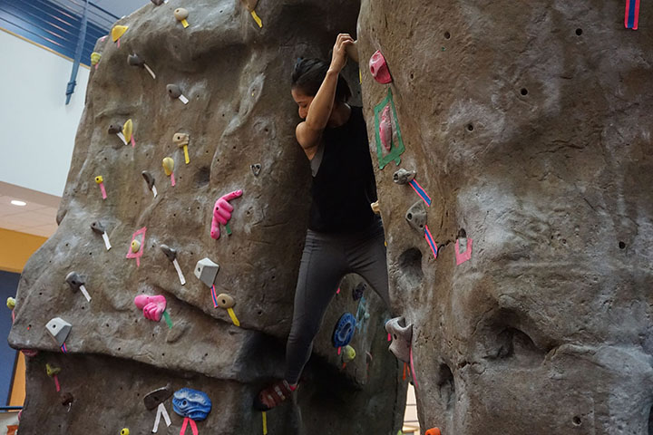 Student Grace Gil triesher luckboulderingon the bouldering wall in the SRC on Thursday Sept.26 2019.