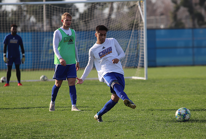Sophomore midfielder Carlos Armendariz scrimmages with teammates during their training practice on Thursday Jan. 30thon the main soccer at CSUB.