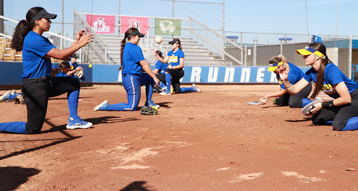 Members+of+the+softball+team+practicing+catching+the+low+balls+during+practice+on+Feb.+12.+