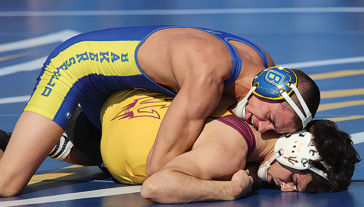Senior Russell Rohlfing pins wrestler from Arizona State during the feud on the field happening on Sunday Feb. 16.