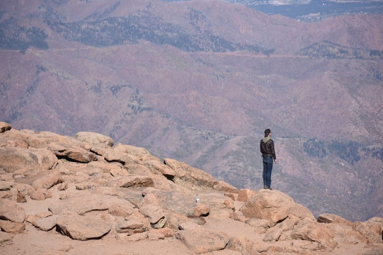 guy standing on big rocks patience and humanity