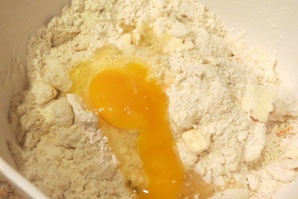 Adding eggs to the flour and butter