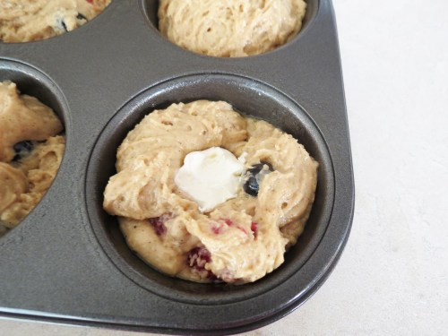 placing cream cheese into muffins