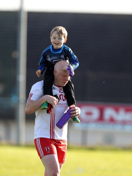 Top scorer Paddy Cunningham carries his son Padraig off the pitch at the end of the game