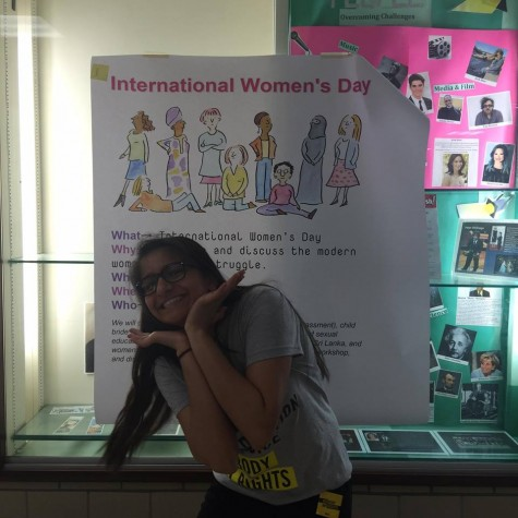 Senior Nawal Wasif, one of the leaders of the event, poses in front of an International Women's Day sign.