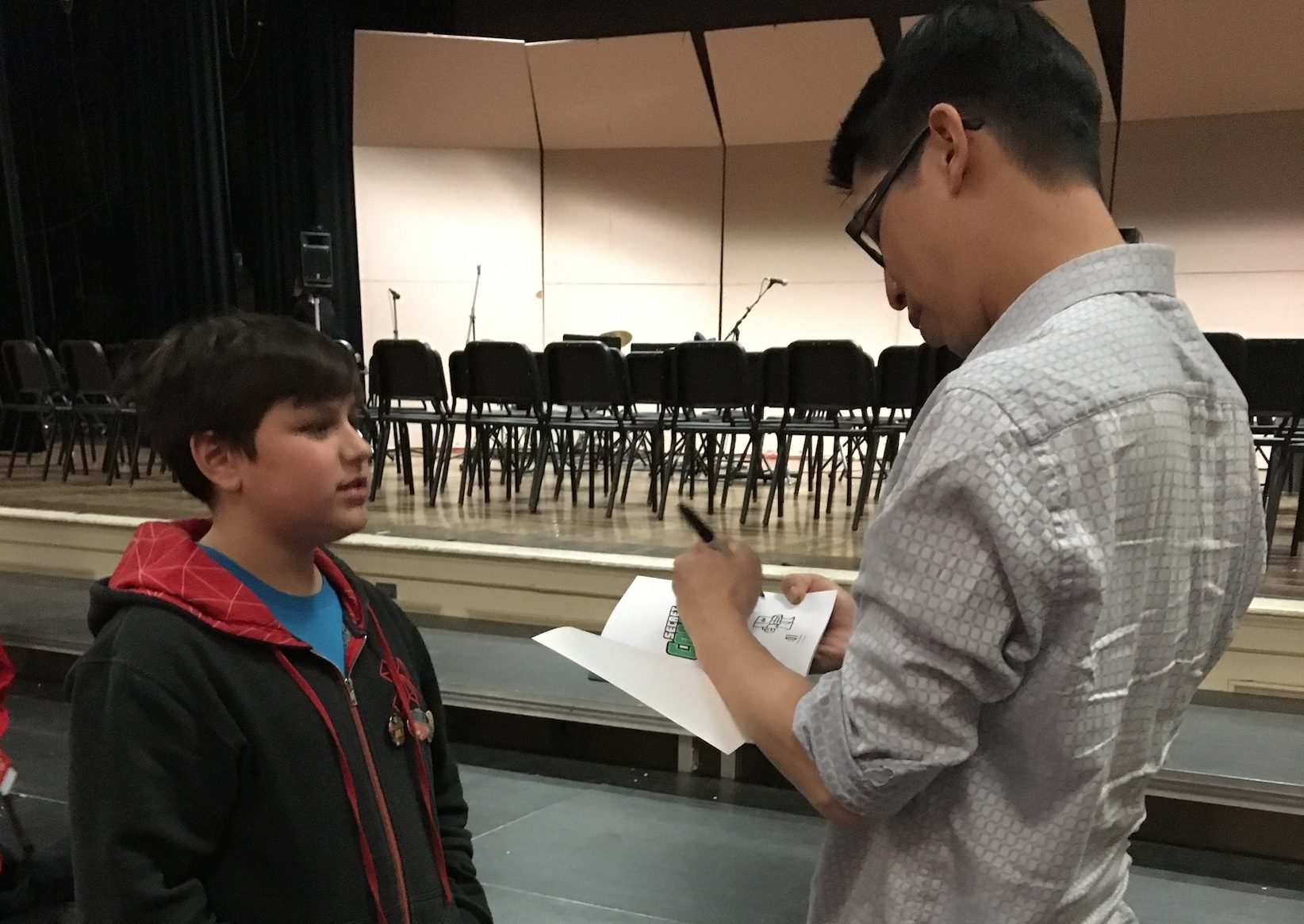 Gene Yang, author of American Born Chinese, signs a book for a young student. Yang addressed both high school and middle school students in the auditorium on April 6.