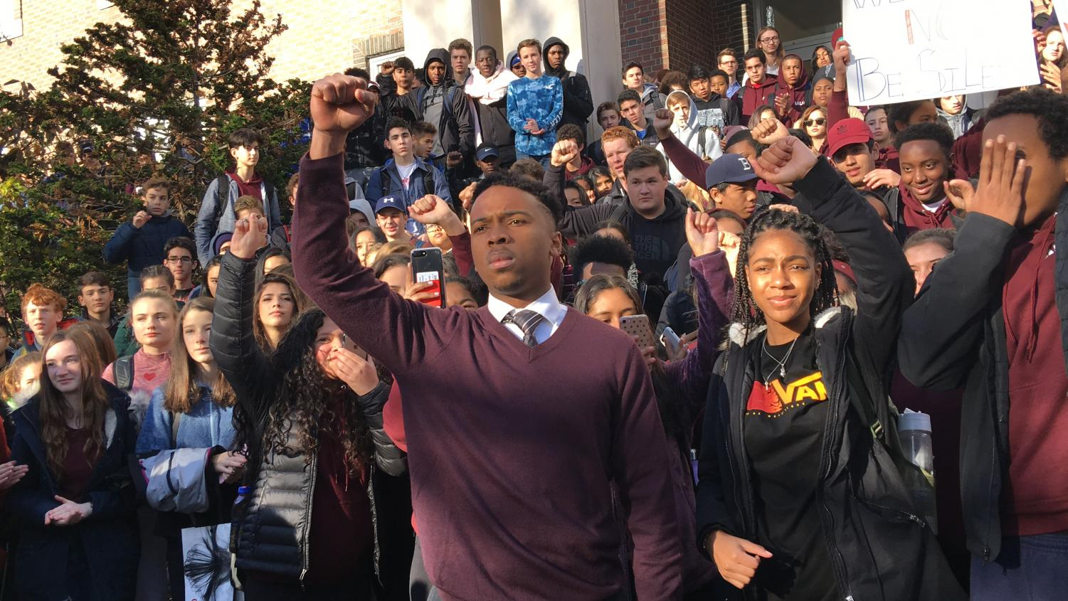 Senior Anthony Vieti leads Thursday's protest against racism by raising his arm in solidarity with the hundreds of community members shocked by the epithet-filled videos. There were two protests, one at 9 a.m. and one at 2 p.m.