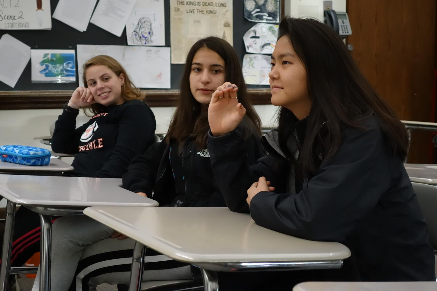 Senior Sophie Arnstein, sophomore Sophie England watch as junior Ling-Li Rotella practices signing in the high school's new ASL class. The class is run through Adult Ed and takes place Tuesday and Wednesday during Z-block.