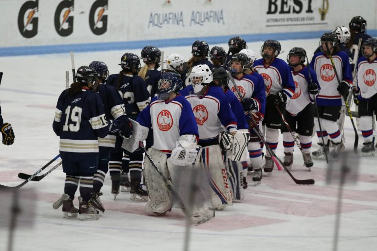 Dressed+in+red%2C+blue+and+orange+jerseys%2C+the+Warrior-Lions+hockey+team+shakes+hands+with+Needham.+The+team+is+comprised+of+athletes+++from+Newton+South+High+School+and+Brookline+High+School.