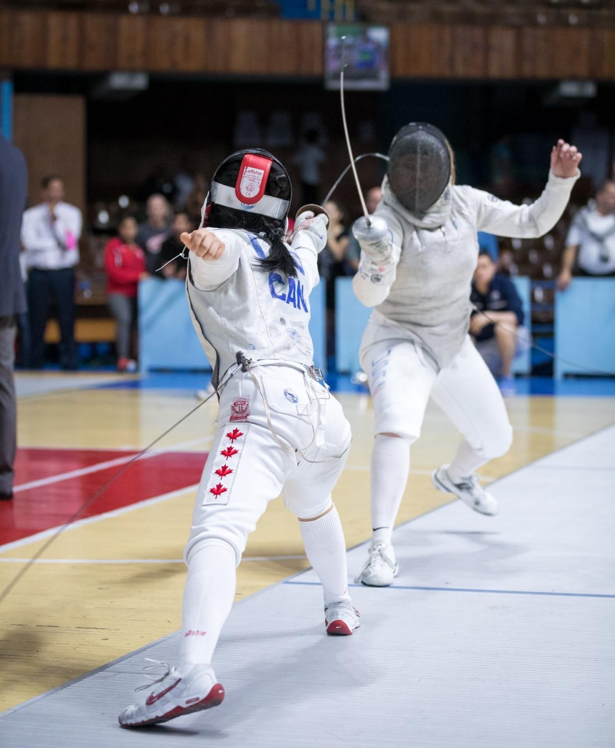Senior Cindy Liu, left, lungs towards her opponent during her fencing match for Canada.