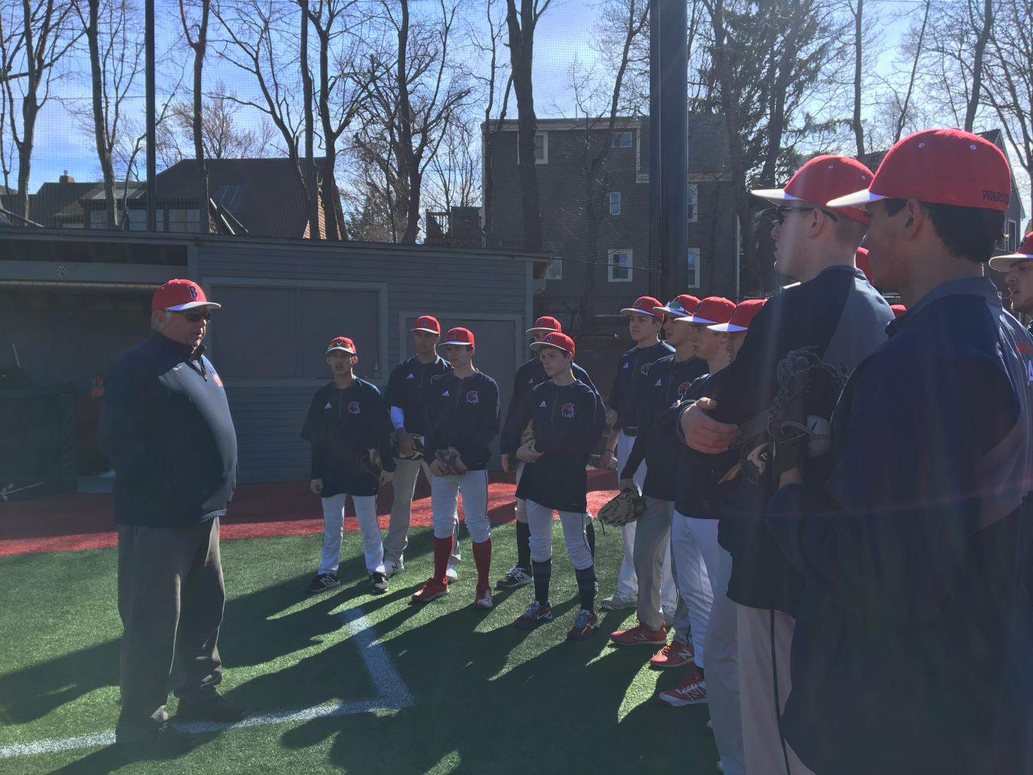 Varsity baseball coach Joe Campagna meets with his team before practice at Parsons Field. Campagna is now retiring after having won over 300 games in his 27 years of coaching.