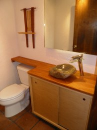 Guest Bathroom. Custom Maple vanity with sliding doors and copper finger pulls. Solid Mahogany counter with stone vessel sink.