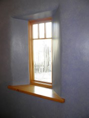 Flared window detail with a Douglas Fir window sill set into a hand finished painted wall.