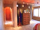 Master Bedroom. Hallway towards bathroom. Curved Adobe wall with exposed brick and glass block.